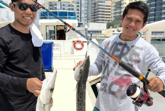 Men Holding there fishing rod and the fishes they caught on their yacht trip